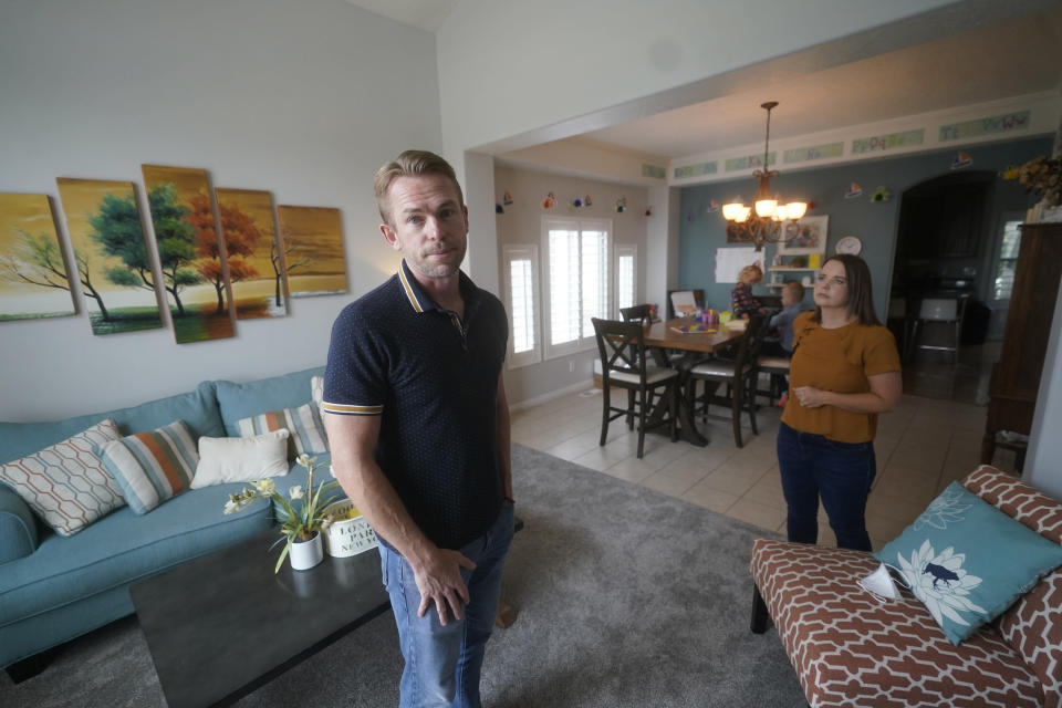 Brad and Stefanie Plothow look on as their children, Cameron, 9, in the 3rd grade, and Ainsley, 5, in kindergarten, are seen in the background, during home schooling, Friday, Aug. 20, 2021, in Lehi, Utah. A group of Utah parents is suing the state over a law that bans school districts from approving mask mandates. It's the latest U.S. legal challenge over rules for face coverings in the classroom. (AP Photo/Rick Bowmer)