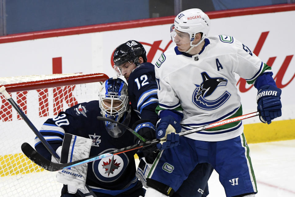 Vancouver Canucks' Tyler Myers (57) checks Winnipeg Jets' Jansen Harkins (12) into Jets goaltender Laurent Brossoit (30) during second-period NHL hockey game action in Winnipeg, Manitoba, Monday, May 10, 2021. (Fred Greenslade/The Canadian Press via AP)
