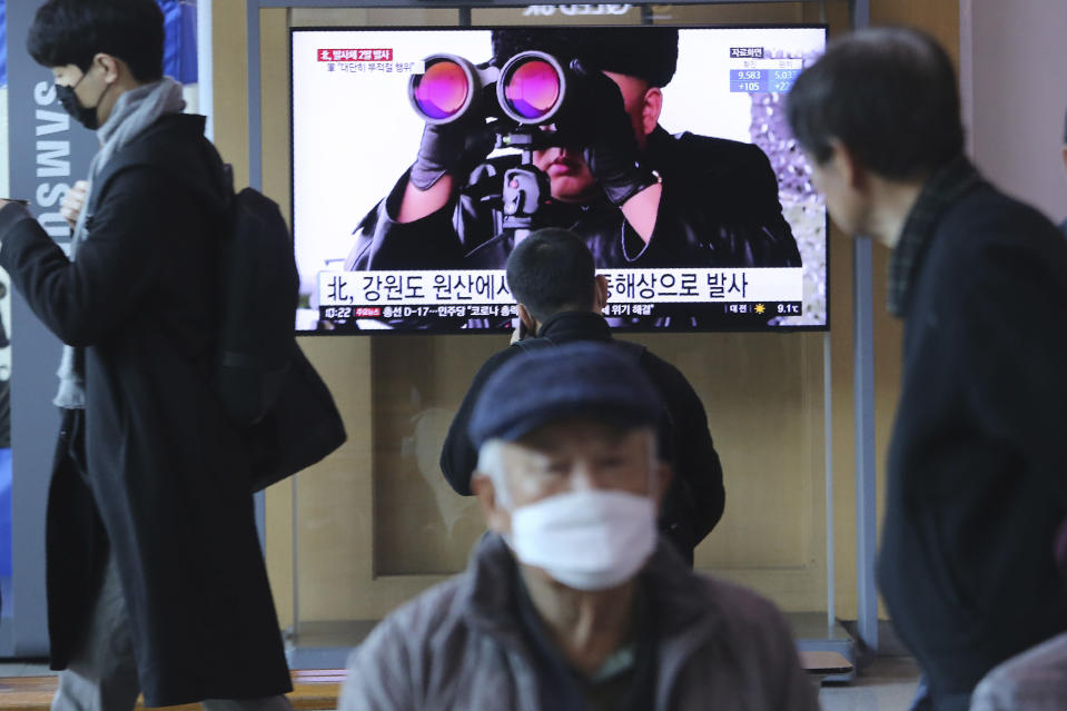 """People pass by a TV screen showing a file image of North Korean leader Kim Jong Un during a news program at the Seoul Railway Station in Seoul, South Korea, Sunday, March 29, 2020. North Korea on Sunday fired two suspected ballistic missiles into the sea, South Korea said, calling it """"very inappropriate"""" at a time when the world is battling the coronavirus pandemic. The Korean letters read: """" North Korea launched two suspected ballistic missiles into the sea."""" (AP Photo/Ahn Young-joon)"""