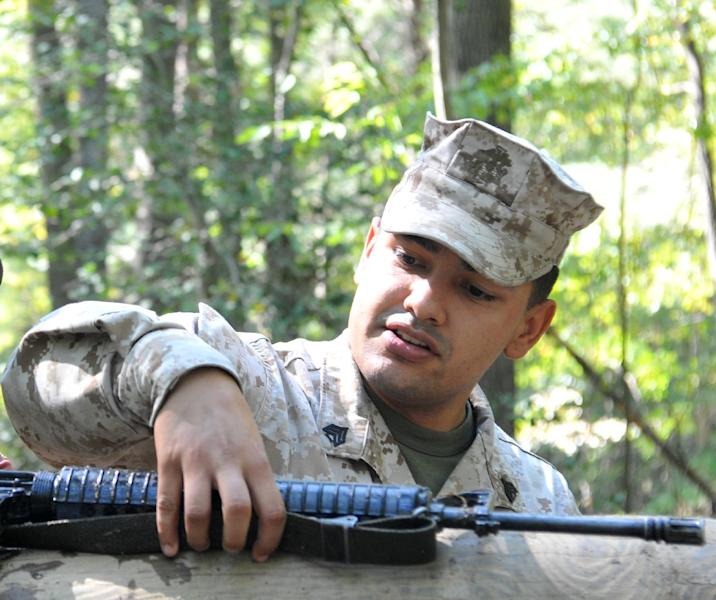 FILE - This Sept. 21, 2012 photo provided by the U.S. Marine Corps shows Sgt. Eusebio Lopez, an Officer Candidate School instructor, during the Quantico Leadership Venture at OCS. Lopez, 25, gunned down 19-year-old Lance Cpl. Sara Castromata and Cpl. Jacob Wooley, 23, on Thursday night March 21, 2013 inside barracks at the Marine Corps Base Quantico in northern Virginia before committing suicide. A July report obtained Thursday, Dec. 12, 2013 by the Associated Press says Lopez had exhibited signs of traumatic brain injury that should have prompted greater concern. (AP Photo/US Marine Corps, Lance Cpl. Antwaun L. Jefferson)