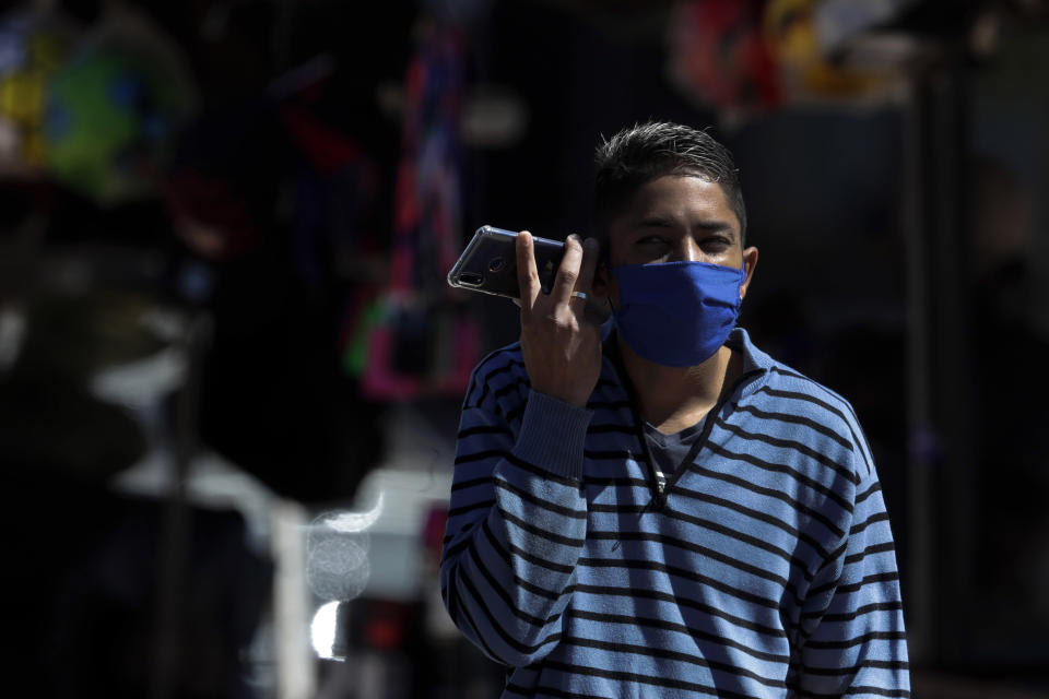 A youth wearing a mask listens to his cell phone in the shopping district of Ceilandia, one of the neighborhoods most affected by the new coronavirus in Brasilia, Brazil, Tuesday, July 21, 2020. (AP Photo/Eraldo Peres)