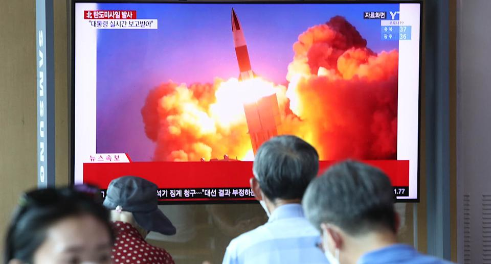 People watch a TV showing a file image of a North Korean missile launch at the Seoul Railway Station on Wednesday