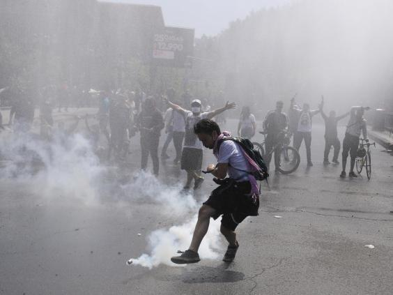 A protester kicks a tear gas canister during clashes in Santiago (AP)