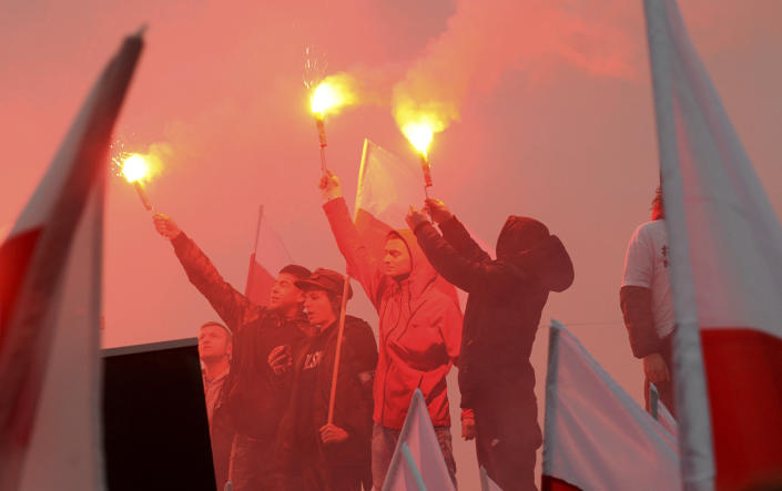 Marchers burn flares in the annual March of Independence organized by far right activists to celebrate 100 years of Poland's independence. The nation of Poland regained its sovereignty at the end of World War I after being wiped off the map for more than a century. (AP Photo/Alik Keplicz)