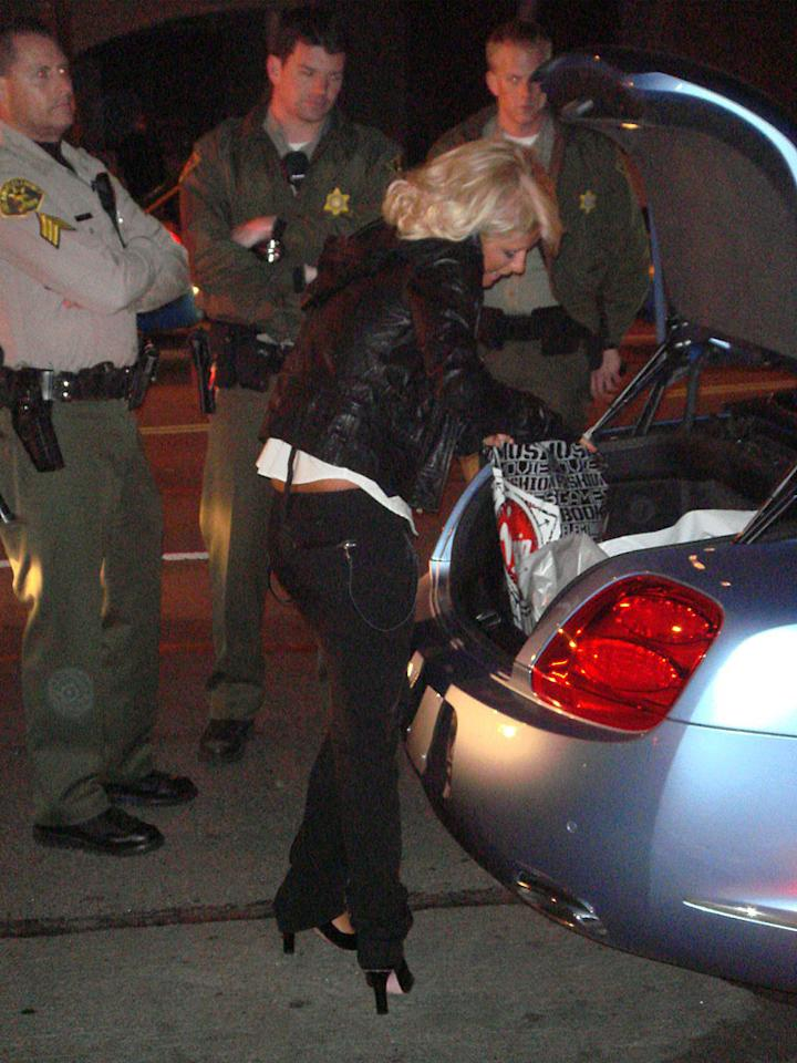 """The police wait patiently as Paris searches through her bags. <a href=""""http://www.x17online.com"""" target=""""new"""">X17 Online</a> - February 27, 2007"""