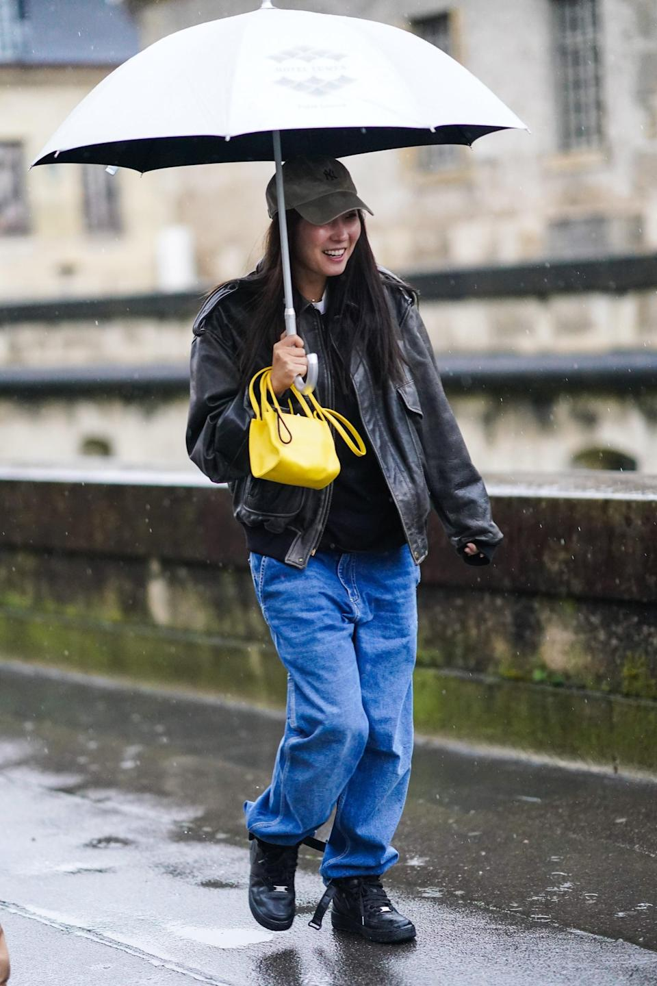 <p>Rain or shine, a pair of baggy jeans is a fail-safe look with sneakers, a baseball hat, and a jacket. A colorful minibag is a fashion-forward finish.</p>