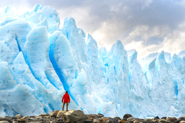 Close-up on man standing in front of blue ice formations of Perito Moreno, Santa Cruz province, Argentina. (Getty)