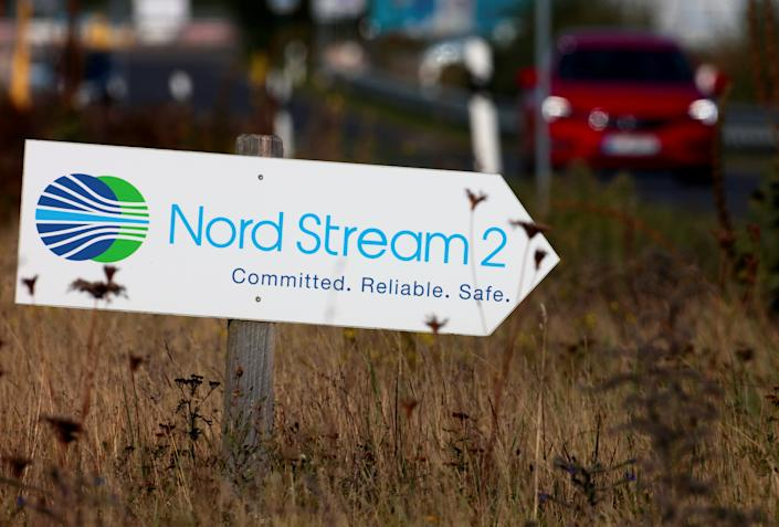 A road sign shaped like an arrow reads: Nord Stream 2. Committed. Reliable. Safe.