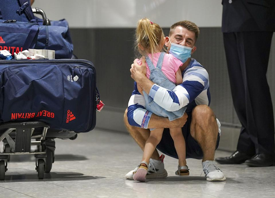 Olympic gymnast Max Whitlock hugs his daughter as he arrives back at London Heathrow Airport from the Tokyo 2020 Olympic Games. Picture date: Tuesday August 3, 2021.