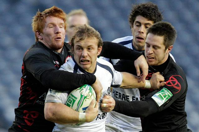 Thomas Sanchou (2nd L) of French rugby club Castres, is tackled by Roddy Grant (L) and John Houston (R), of Scottish team Edinburgh during a Heineken Cup, pool one, rugby union match at Murrayfield, Edinburgh, Scotland, on December 20, 2010. The game went ahead Monday, after being having been postponed due to bad weather on Sunday. AFP PHOTO/GRAHAM STUART (Photo credit should read GRAHAM STUART/AFP/Getty Images)