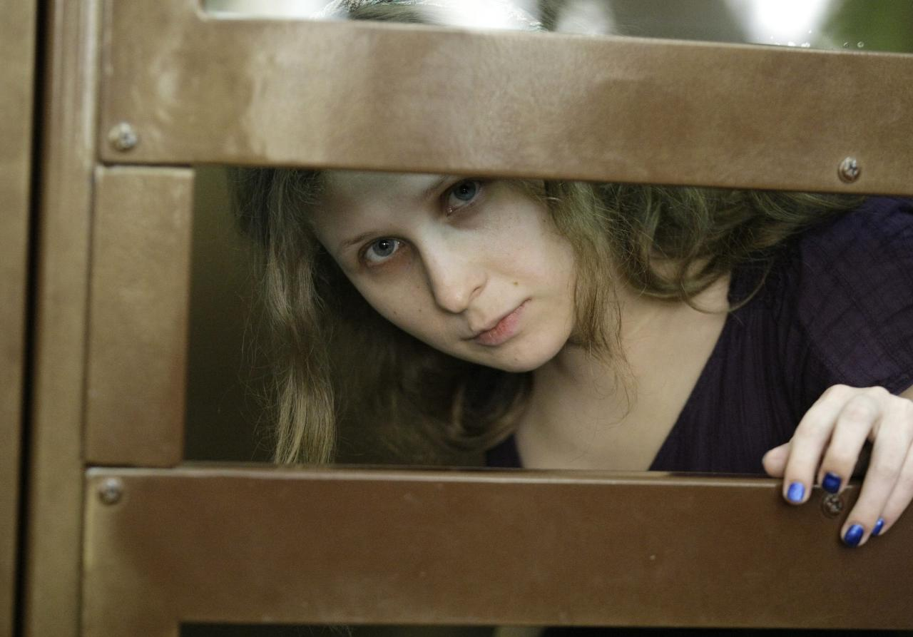 "Yekaterina Samutsevich member of feminist punk group Pussy Riot looks on as she stand behind bars in a court in Moscow, Russia, Russia, Monday, July 30, 2012. Three members of the band are facing trial for performing a ""punk prayer"" against Vladimir Putin from a pulpit of Moscow's main cathedral before Russia's presidential election in March, in which he won a third term. (AP Photo/Mikhail Metzel)"