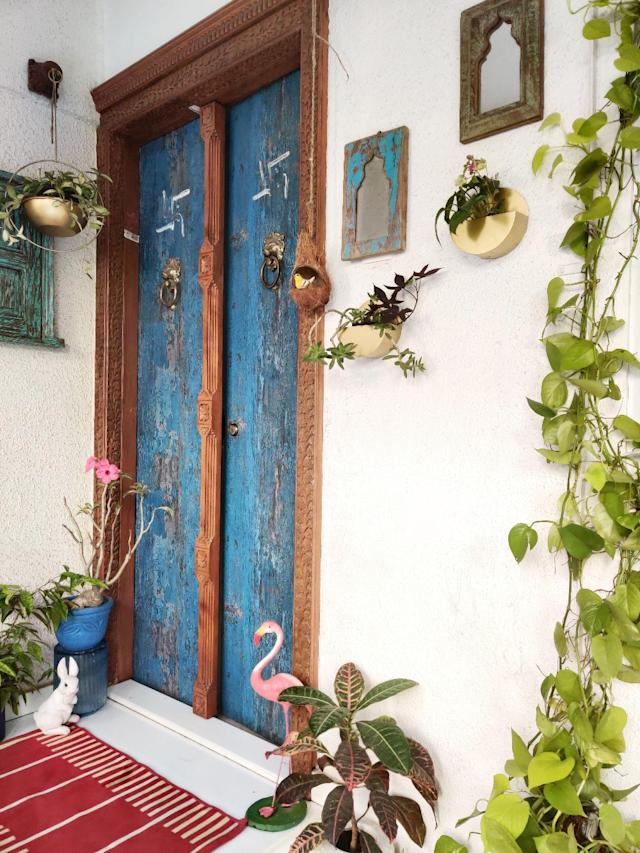 The main entrance to the row house features a carved wooden door frame, mirrors framed in distressed wood and myriad plants.