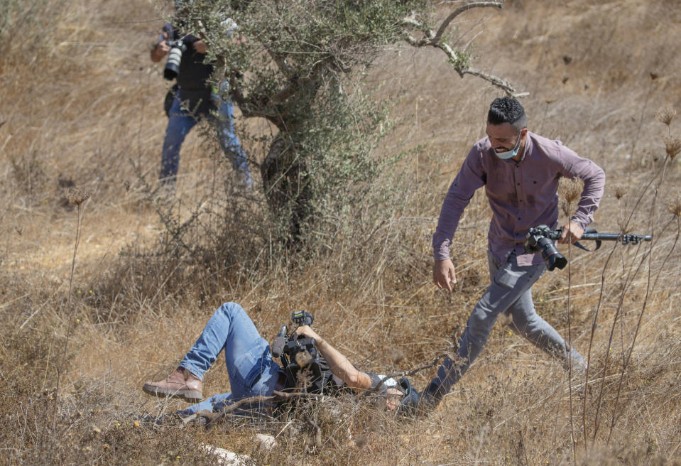 A journalist rushes to help his fellow cameraman after Israeli border police dispersed journalists using stun grenades and teargas, in the West Bank village of Burqa, East of Ramallah, Friday, Oct. 16, 2020. Palestinians clashed with Israeli border police in the West Bank on Friday during their attempt to reach and harvest their olive groves near a Jewish settlers outpost. (AP Photo/Nasser Nasser)