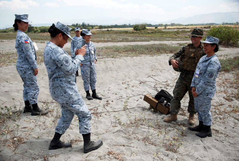FILE PHOTO: A Filipina soldier gets her photo taken with an American soldier after amphibious landing exercises during U.S.-Philippines war games promoting bilateral ties in Zambales province, Philippines
