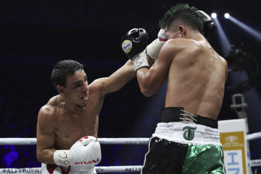France's Nordine Oubaali, left, sends a left to Japan's Takuma Inoue in the seventh round of their WBC world bantamweight title match in Saitama, Japan, Thursday, Nov. 7, 2019. Oubaali defeated Inoue by a unanimous decision. (AP Photo/Toru Takahashi)