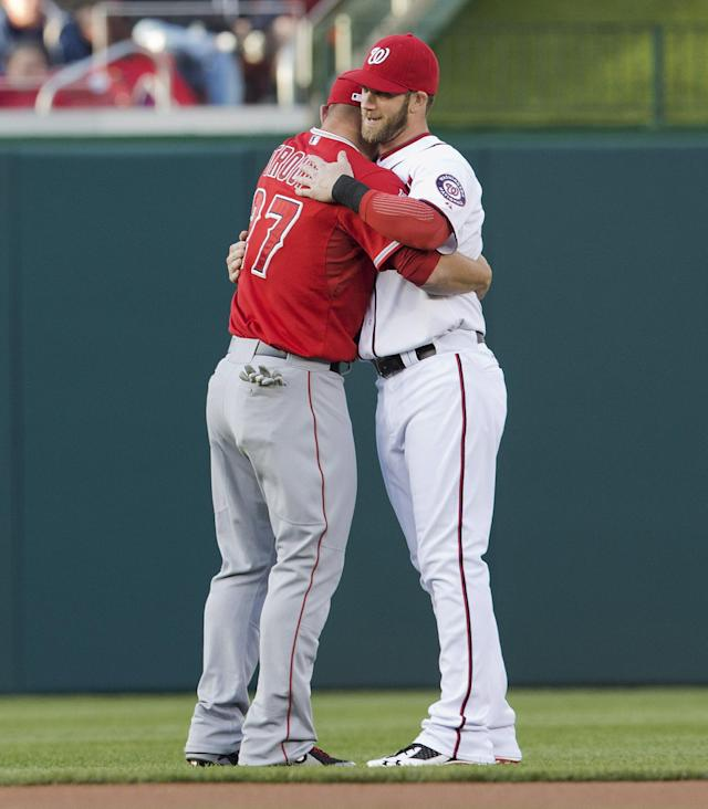 Los Angeles Angels'Mike Trout, left, and Washington Nationals' Bryce Harper, right, hug during warm-ups before a baseball game, Wednesday, April 23, 2014, in Washington. (AP Photo/Pablo Martinez Monsivais)