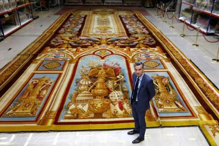 Herve Lemoine, head of the Mobilier National and the Gobelins Manufactury, poses in front of the 19th century choir carpet of Notre-Dame de Paris Cathedral,