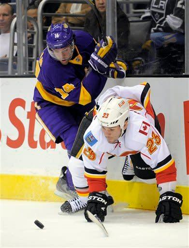 Calgary Flames defenseman Scott Hannan, right, falls as he battles for the puck with Los Angeles Kings right wing Justin Williams during the second period of an NHL hockey game Saturday, Feb. 18, 2012, in Los Angeles. (AP Photo/Mark J. Terrill)