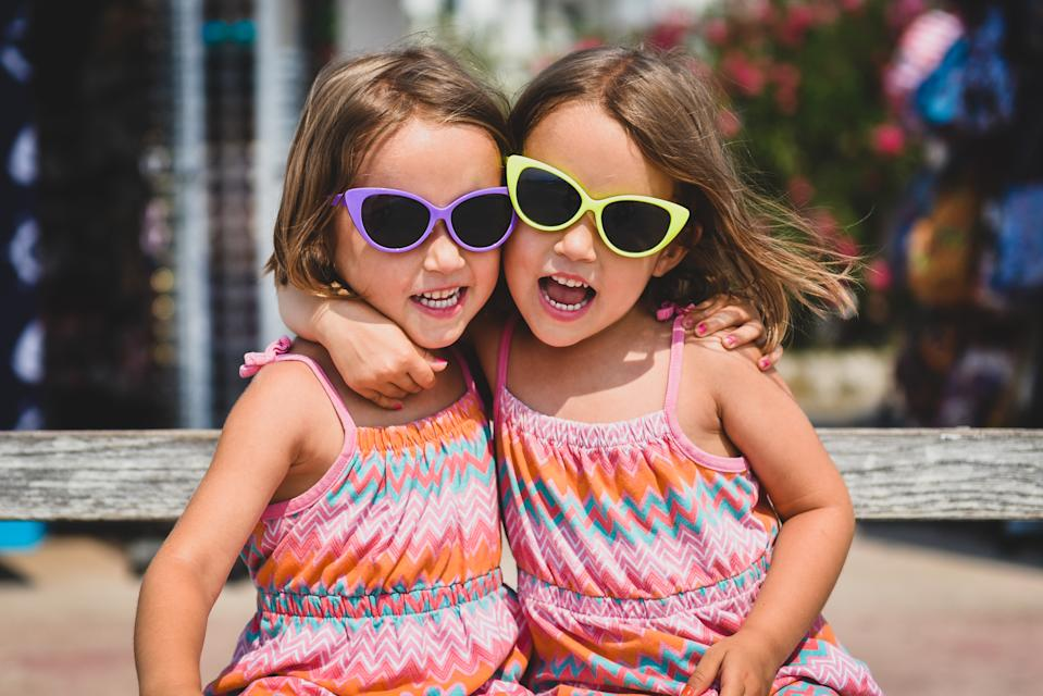 Identical twin girls on summer vacation posing for camera. Happy joyful children in the summertime with child sun glasses and pink dresses.