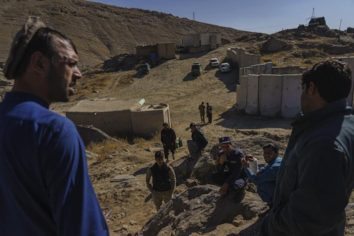 Afghan National Police commander Sarda Wali speaks to his men, standing in an area of bare dirt hills.