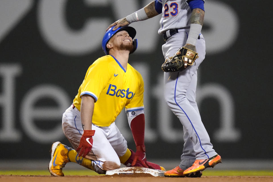 Boston Red Sox catcher Christian Vazquez, left, gets a congratulatory pat on the head by New York Mets second baseman Javier Baez (23) after his RBI double in the fourth inning of a baseball game at Fenway Park, Tuesday, Sept. 21, 2021, in Boston. (AP Photo/Charles Krupa)