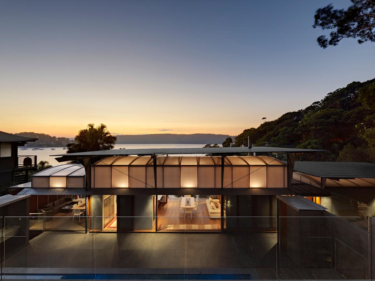 Built with Fergus Scott Architects, Cliff Face House in Palm Beach, New South Wales, incorporates the sandstone rock face into the structure of the home. A polycarbonate vault filters soft light into the living areas and ventilation holes cool the house naturally.