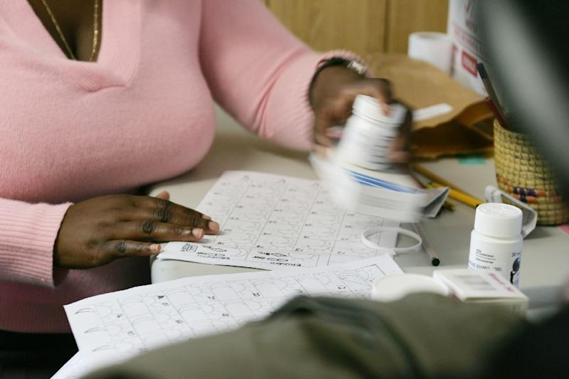 A nurse (L) explains to a patient how to take antiretroviral drugs, at a hospital in Winterton, South Africa