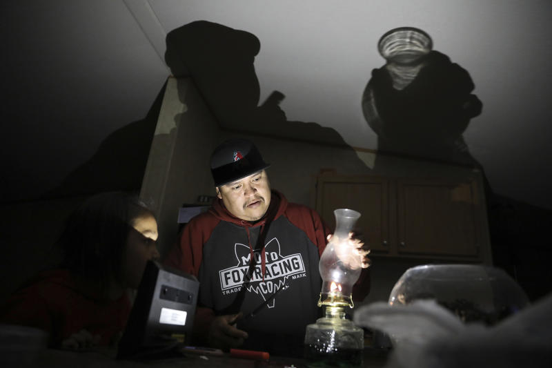 In this Wednesday, May 8, 2019 photo Jimmie Long Jr. places the glass on an oil lamp inside his Kaibeto home on the Navajo Reservation in Arizona. Long and his wife, Miranda Haskie, were spending one last night without electricity in their home before being connected to the grid on Thursday, May 16, 201. An ambitious project to connect homes to the electric grid on the country's largest American Indian reservation is wrapping up. Utility crews from across the U.S. have volunteered their time over the past few weeks to hook up about 300 homes on the Navajo Nation. (AP Photo/Jake Bacon)