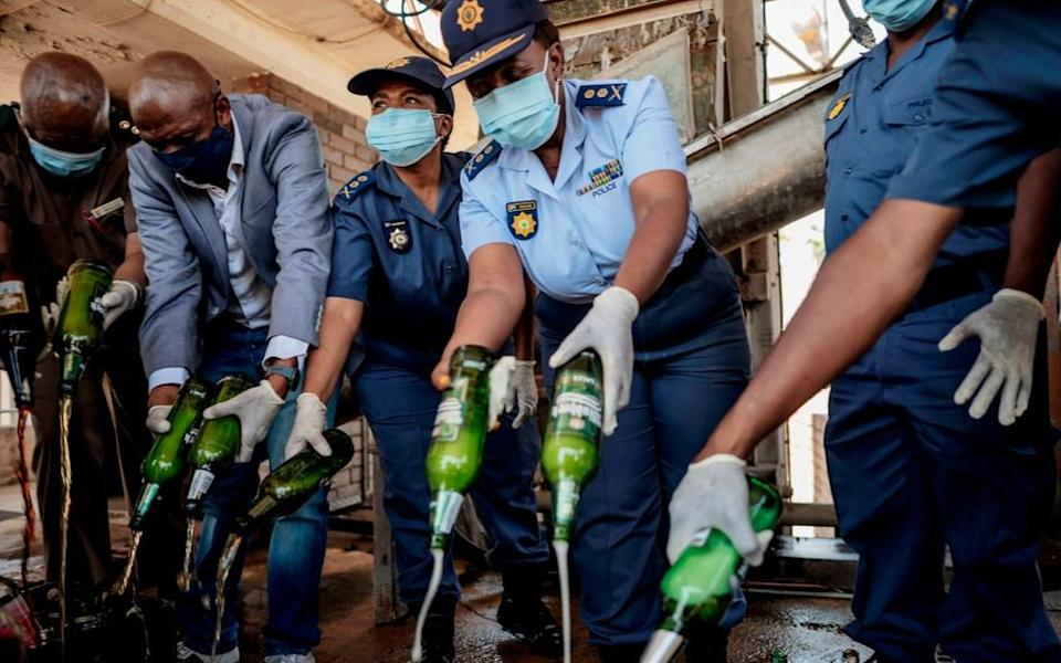 South African Police Service (SAPS) officers destroy some 2000 litres of illegal alcohol confiscated during various operations, at Tshwane, on October 30, 2020.