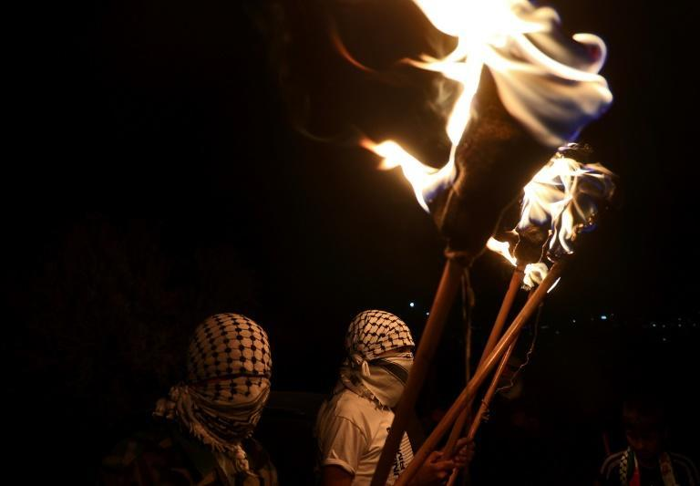 Palestinian protesters hold torches during a demonstration against the Israeli settler outpost of Eviatar on June 28, 2021