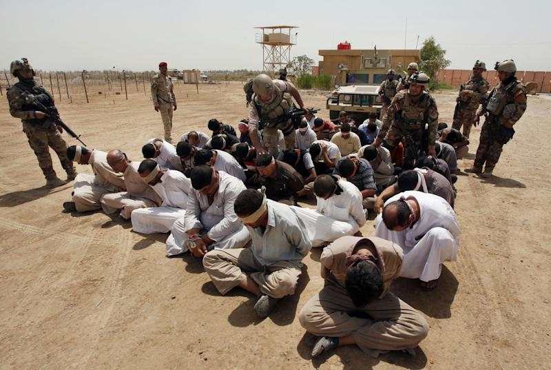 FILE - In this Friday, July 20, 2012 file photo, blindfolded and handcuffed suspected al-Qaida members are guarded by Iraqi army soldiers in an Iraqi army base in Hillah, Iraq. Al-Qaida's branch in Iraq claimed responsibility on Monday for the killing last week of 48 Syrian soldiers and nine Iraqi guards in western Anbar province. (AP Photo/ Alaa al-Marjani, File)