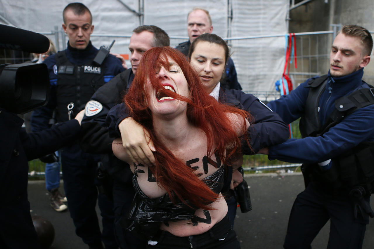 <p>A Femen activist is led away by French police in Hénin-Beaumont, northern France, May 7, 2017. Voters across France chose a new president in an unusually tense and important election that could decide Europe's future, making a stark choice between pro-business progressive candidate Emmanuel Macron and far-right populist Marine Le Pen. (Francois Mori/AP) </p>