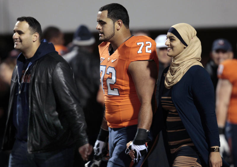 FILE - This Nov. 15, 2012, file photo, shows Virginia offensive tackle Oday Aboushi and his family as they are introduced prior to an NCAA college football game at Scott stadium in Charlottesville, Va. The big offensive lineman, a potential first-round pick in the NFL draft in April, returned to Staten Island on Saturday, Dec. 22, 2012 to try to lend a helping hand to those affected by the storm _ some of them his friends and neighbors. (AP Photo/Steve Helber, File)