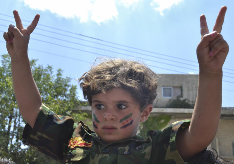 This citizen journalism image released by Shaam News Network taken Friday, July 6, 2012 purports to show a child in a military uniform and flashing the victory sign at an anti-Assad protest in Kafr Nabil, in Northwestern Syria. (AP Photo/Ra'ed Alfares, Shaam News Network) THE ASSOCIATED PRESS IS UNABLE TO INDEPENDENTLY VERIFY THE AUTHENTICITY, CONTENT, LOCATION OR DATE OF THIS CITIZEN JOURNALISM IMAGE