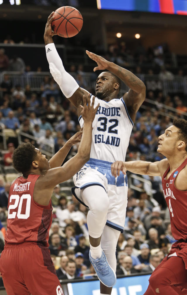 Rhode Island's Jared Terrell (32) shoots between Oklahoma's Kameron McGusty (20) and Jamuni McNeace (4) during the first half in the first round of the NCAA men's college basketball tournament, Thursday, March 15, 2018, in Pittsburgh. (AP Photo/Keith Srakocic)
