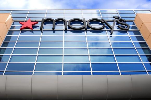 A Macy's store sign viewed up from street level.