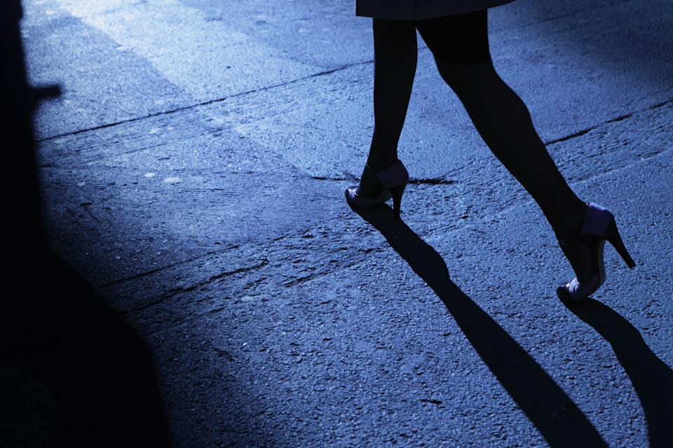 A woman is seen walking at night. (Getty)