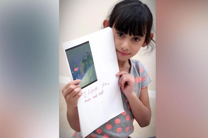 Sophia pictured smiling and holding a homemade card for her parents bearing the message:
