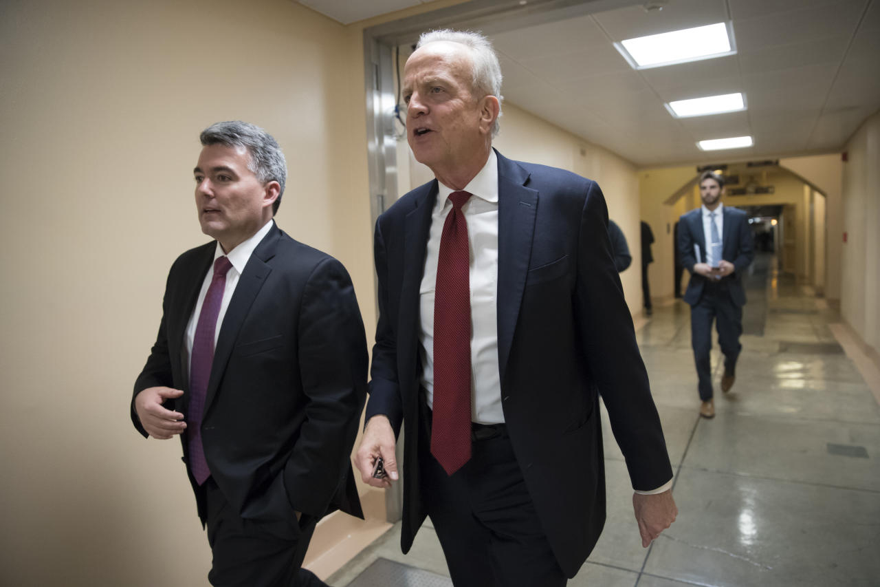 Sen. Cory Gardner, R-Colo., left, and Sen. Jerry Moran, R-Kan., return to their offices on Capitol Hill as Congress moves closer to the deadline to avoid a government shutdown, in Washington, Thursday, Jan. 18, 2018. (AP Photo/J. Scott Applewhite)