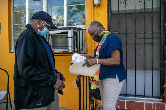 Linda Mallard and her father, John Palmer, look through eviction paperwork in front of an apartment in a building they own in the Little River neighborhood of Miami. They hired an eviction company to boot out the tenant living at that apartment, who stopped paying rent in February.