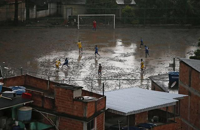 RIO DE JANEIRO, BRAZIL - MARCH 23: People play soccer on a muddy field in the Complexo do Alemao pacified 'favela' community on March 23, 2014 in Rio de Janeiro, Brazil. The 'favela' was previously controlled by drug traffickers and is now occupied by the city's Police Pacification Unit (UPP). A number of UPP's were attacked by drug gang members on March 20 and some pacified favelas will soon receive federal forces as reinforcements. The UPP are patrolling some of Rio's favelas amid the city's efforts to improve security ahead of the 2014 FIFA World Cup and 2016 Olympic Games. (Photo by Mario Tama/Getty Images)