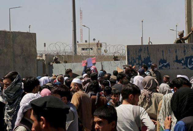 US soldiers stand inside the airport wall as hundreds of people gather near an evacuation control checkpoint on the perimeter of the Hamid Karzai International Airport, in Kabul, Afghanistan, Thursday, Aug. 26, 2021 (Photo: via Associated Press)