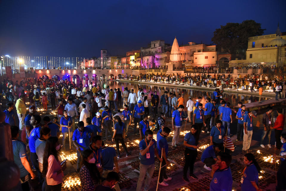People light lamps on the banks of river Saryu in Ayodhya, India, Friday, Nov. 13, 2020. The northern Indian city of Ayodhya kept its Guinness World Record for a second straight year by lighting more than 584,572 oil lamps and keeping them burning for at least 45 minutes on the banks of the river Saryu as part of the celebration of Diwali, the annual Hindu festival of lights. (AP Photo/Rajeev Bhatt)