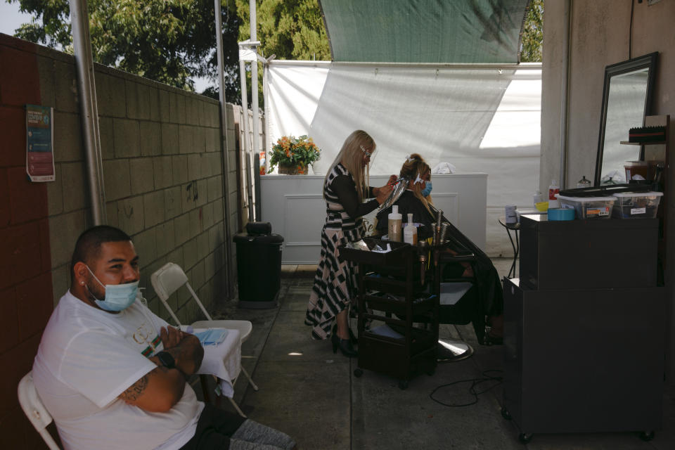 Mario Perez, 32, left, sits on a chair while his wife, Jocelyn, gets her hair bleached at an outdoor hair salon in the Watts neighborhood of Los Angeles, Monday, Aug. 3, 2020. Watts has changed demographically from an exclusively Black neighborhood in the '60s to one that's majority Latino. But it remains a poor neighborhood with high unemployment. (AP Photo/Jae C. Hong)