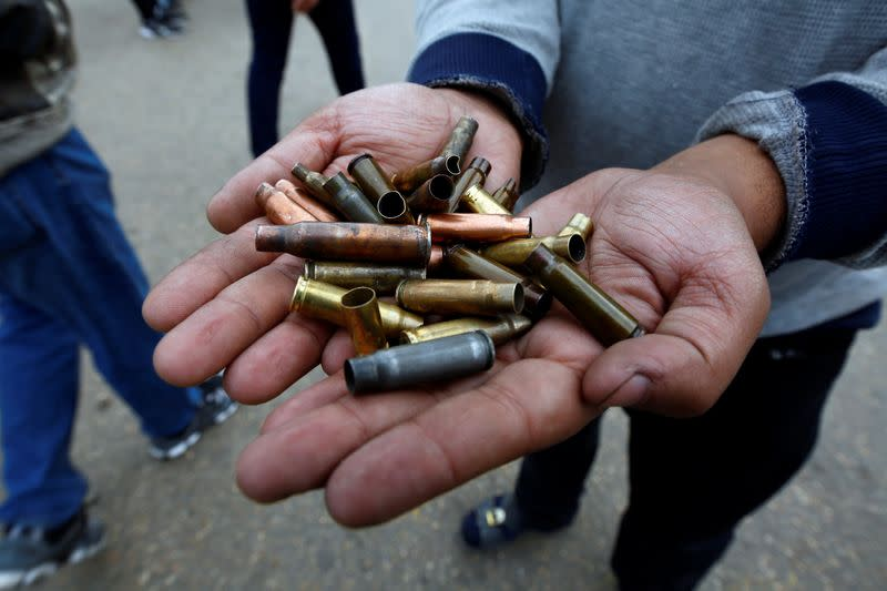 Man shows the casings from bullets which were allegedly used against protesters who were killed at an anti-government protest overnight in Najaf