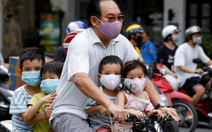 Children are protected with a mask as they travel in Hanoi, Vietnam - REUTERS/Kham