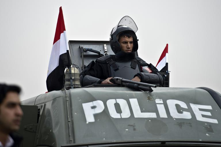 An policeman stands guard on the top of an armoured vehicle in Cairo on February 16, 2014