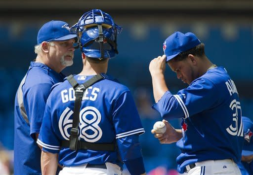Toronto Blue Jays pitching coach Bruce Walton, left, comes out to talk with Blue Jays starting pitcher Henderson Alvarez, right, while Blue Jays catcher Yan Gomes listens as they play against the Texas Rangers during third-inning baseball game action in Toronto, Sunday, Aug. 19, 2012. (AP Photo/The Canadian Press, Nathan Denette)