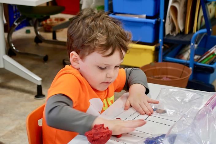 Children in Mineola's preschool program create letters using clay.