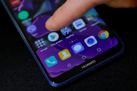 A man points a finger to the Google Play app logo on his Huawei smartphone in this illustration picture  May 20, 2019. REUTERS/Marko Djurica/Illustration